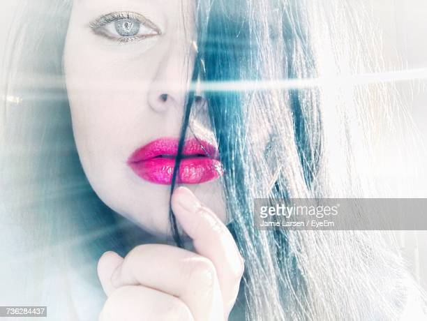 Close-Up Portrait Of Woman With Pink Lipstick On Sunny Day