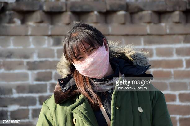 close-up portrait of woman with pollution mask standing against brick wall - masque tissus photos et images de collection