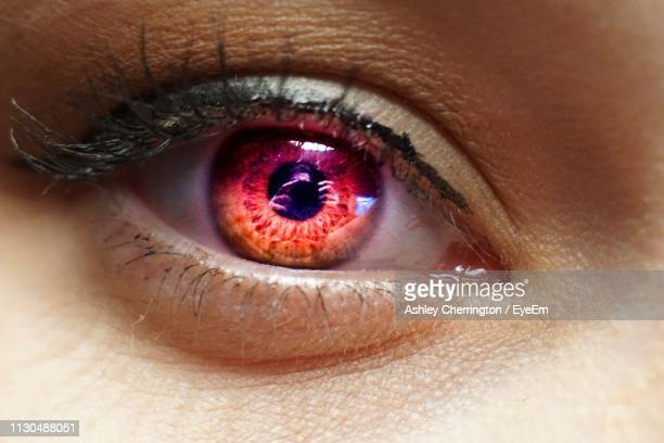 close-up portrait of woman with red eye - bloodshot stock pictures, royalty-free photos & images
