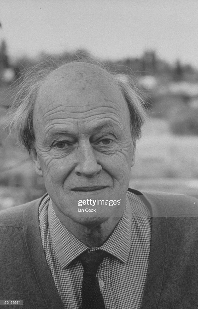 Closeup portrait of writer Roald Dahl slightly smiling while standing outside his home in Great Missenden, Buckinghamshire, England.