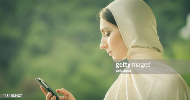closeup portrait of young attractive muslim female in hijab typing phone - iranian culture stock pictures, royalty-free photos & images