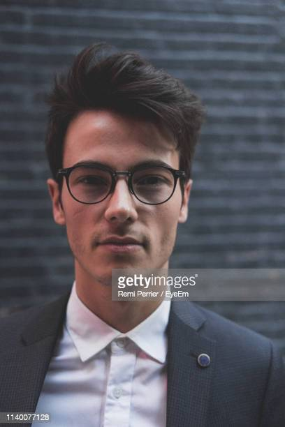 close-up portrait of young businessman wearing eyeglasses against wall - menswear stock pictures, royalty-free photos & images