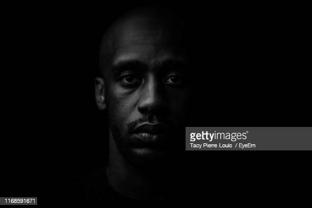 close-up portrait of young man against black background - black photos et images de collection