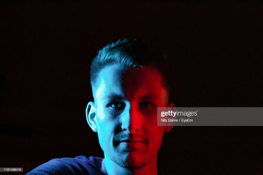 Close-Up Portrait Of Young Man Against Black Background : Stock Photo