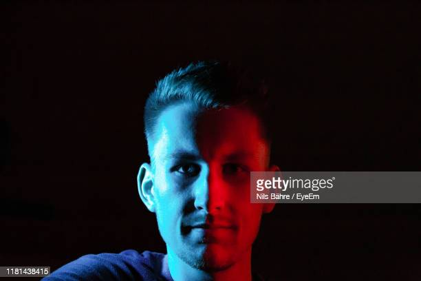 close-up portrait of young man against black background - portrait blue background stock pictures, royalty-free photos & images