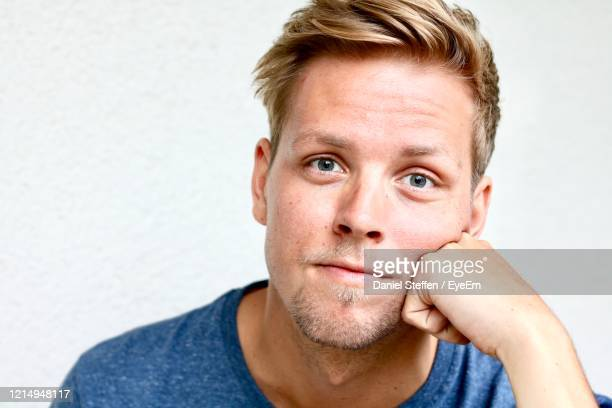 close-up portrait of young man against white background - 顎に手をやる ストックフォトと画像