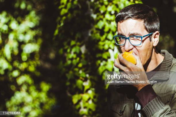 Close-Up Portrait Of Young Man Eating Fruit While Standing Against Plants
