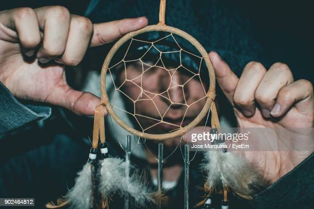 Close-Up Portrait Of Young Man Looking Through Dreamcatcher