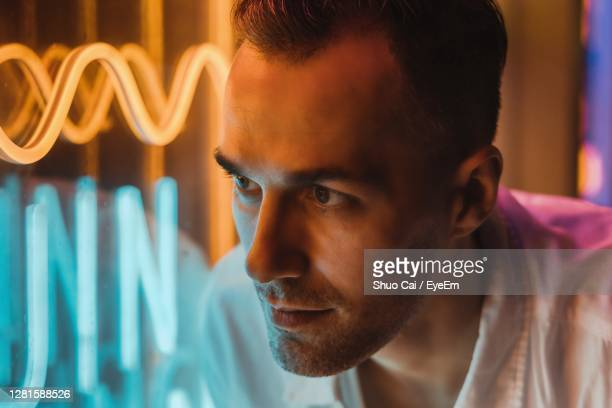 close-up portrait of young man next to neon light - human body part stock pictures, royalty-free photos & images