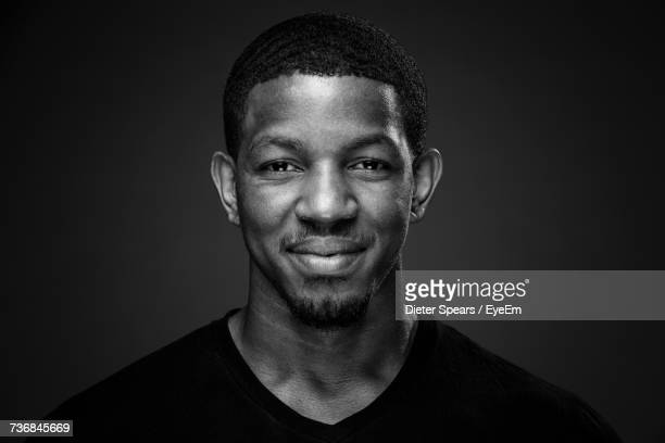 close-up portrait of young man smiling while standing against black background - black and white ストックフォトと画像