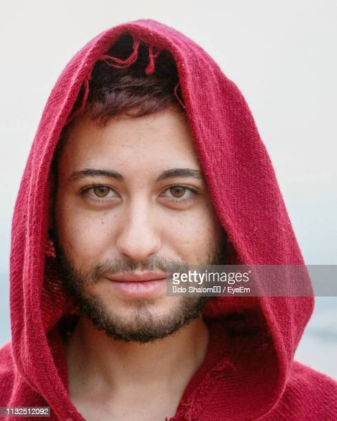close-up portrait of young man wearing red hooded shirt outdoors - hooded top stock pictures, royalty-free photos & images