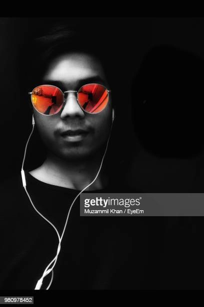 close-up portrait of young man wearing sunglasses while listening music on in-ear headphones against black background - isolated color stock pictures, royalty-free photos & images