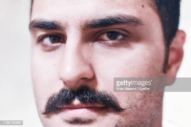 close-up portrait of young man with mustache - moustache stock pictures, royalty-free photos & images