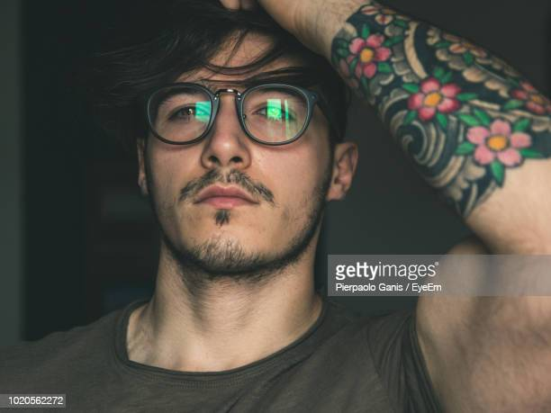 close-up portrait of young man with tattoo wearing eyeglasses at home - affascinante foto e immagini stock