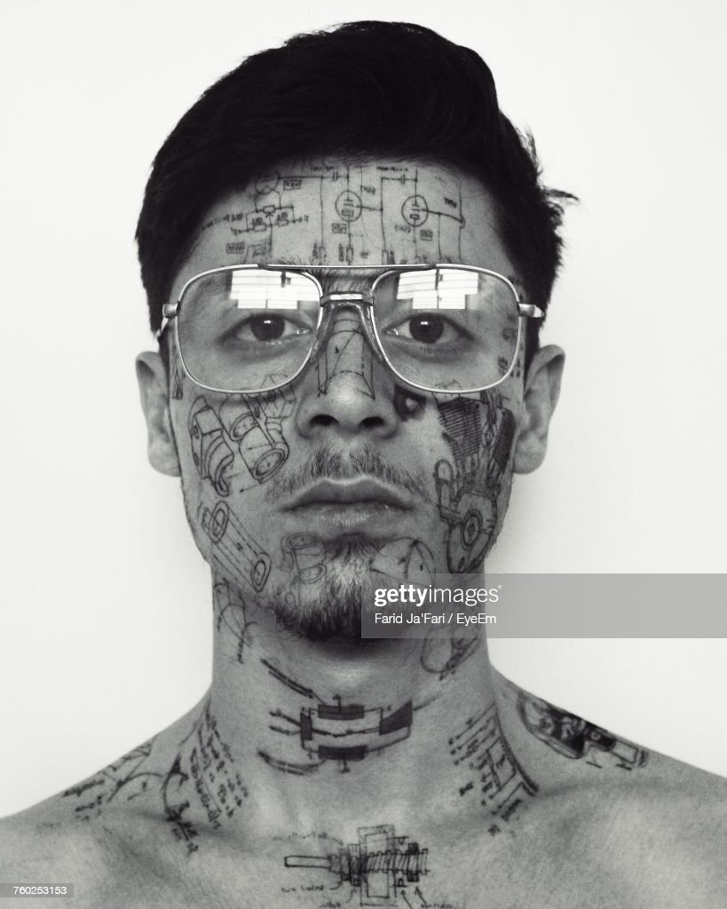 Close-Up Portrait Of Young Man With Tattoos On Face Against White Background : Stock Photo