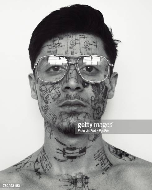 Close-Up Portrait Of Young Man With Tattoos On Face Against White Background
