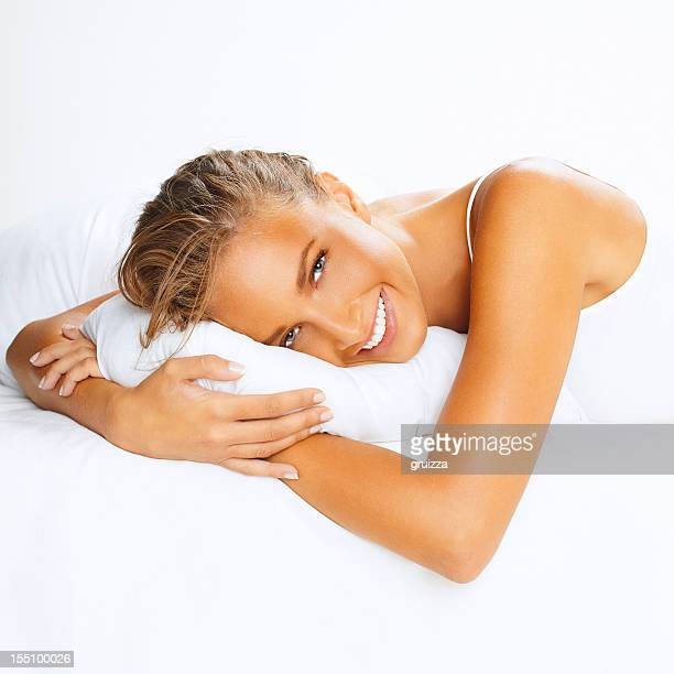 Close-up, portrait of young, smiling woman on bed, hugging pillow