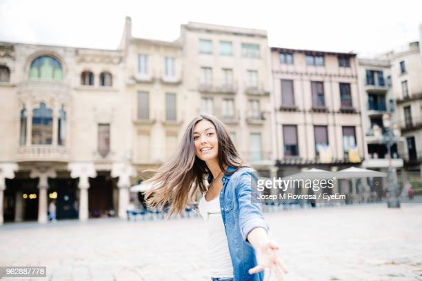 close-up portrait of young woman against buildings in city - reus spain ストックフォトと画像