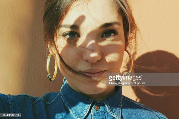 close-up portrait of young woman against wall - earring stock pictures, royalty-free photos & images