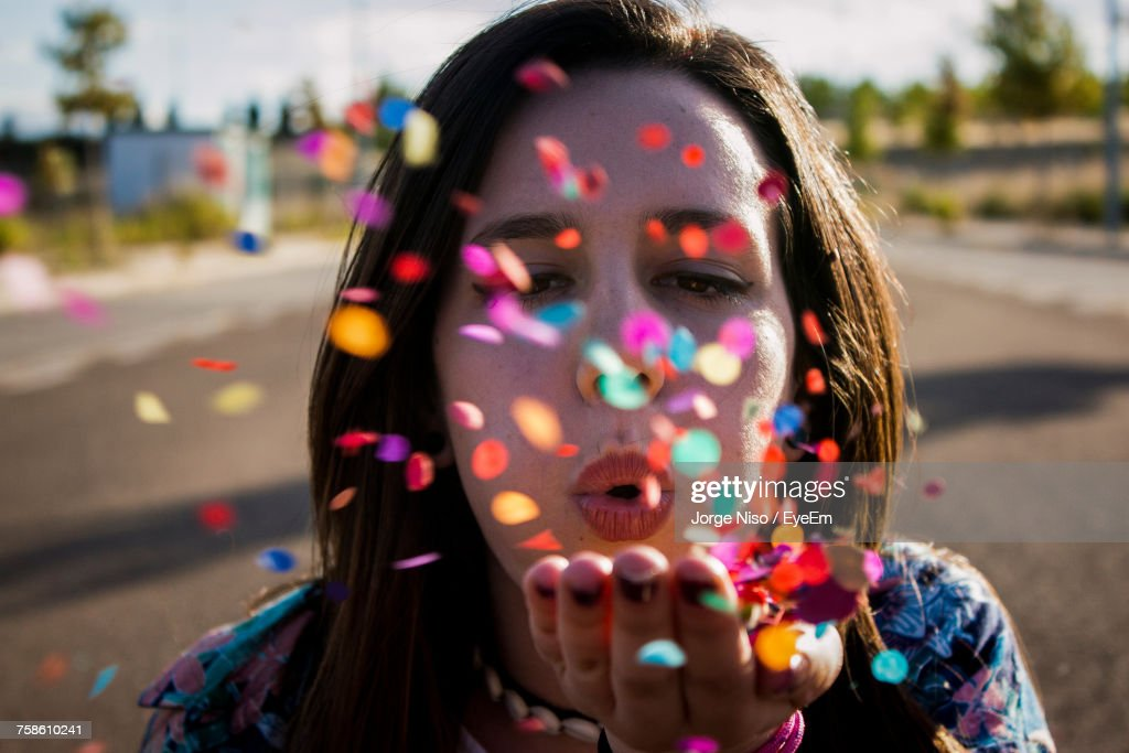 Close-Up Portrait Of Young Woman Blowing Confetti : Stock-Foto