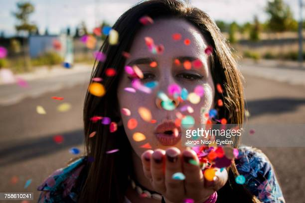 Close-Up Portrait Of Young Woman Blowing Confetti