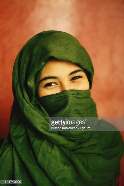 close-up portrait of young woman covering face with textile - headscarf stock pictures, royalty-free photos & images
