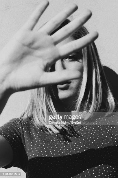close-up portrait of young woman gesturing while standing against wall - obscured face stock pictures, royalty-free photos & images
