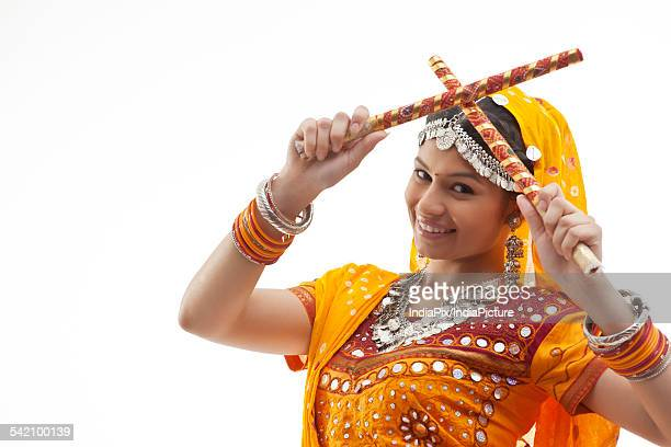 Close-up portrait of young woman holding dandiyas isolated over white background