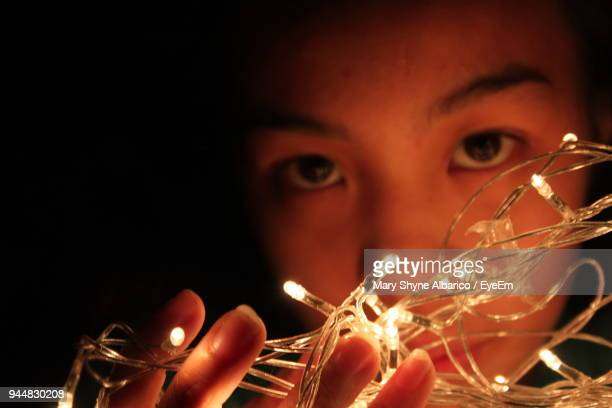 close-up portrait of young woman holding illuminated string lights in darkroom - mary moody fotografías e imágenes de stock