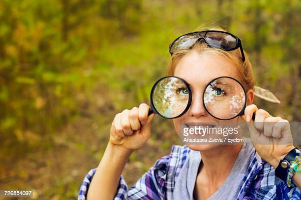Close-Up Portrait Of Young Woman Holding Magnifying Glasses In Forest