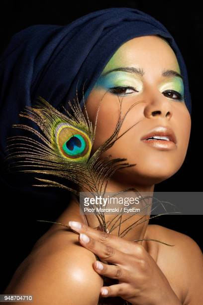 close-up portrait of young woman holding peacock feather against black background - eye make up stock pictures, royalty-free photos & images