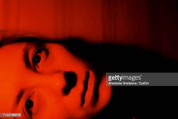 close-up portrait of young woman in illuminated room - junge frau rätsel stock-fotos und bilder