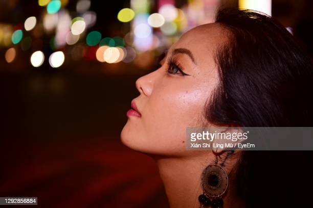 close-up portrait of young woman looking away - 歓楽街 ストックフォトと画像