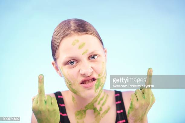 close-up portrait of young woman showing obscene gesture against blue background - kid middle finger stock pictures, royalty-free photos & images