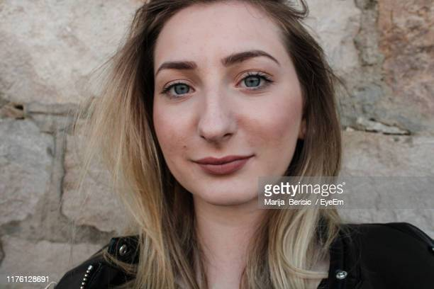 close-up portrait of young woman smiling against wall - marija mauer stock-fotos und bilder