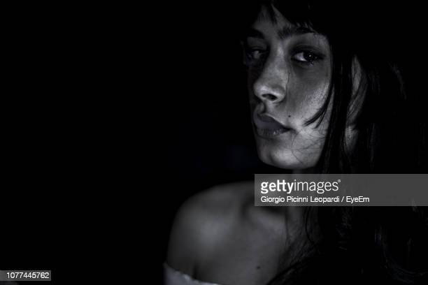 Close-Up Portrait Of Young Woman Smoking Against Black Background