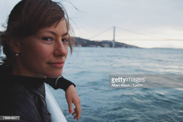 Close-Up Portrait Of Young Woman Traveling On Ferry At Sea Against Bridge