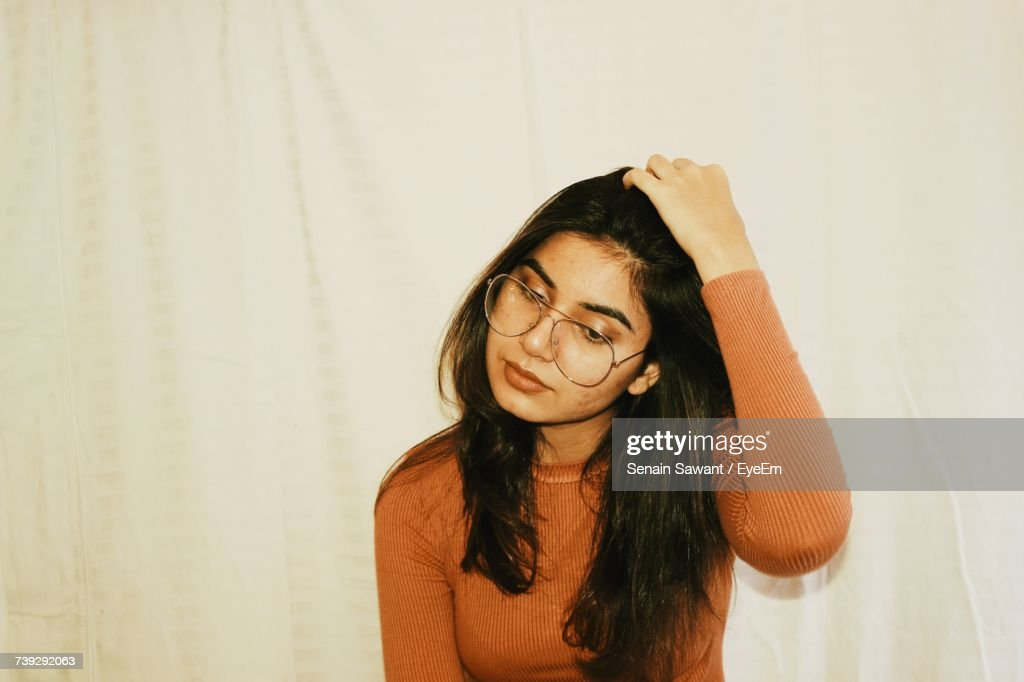 Close-Up Portrait Of Young Woman Wearing Eyeglasses Standing Against Curtain : Stock Photo