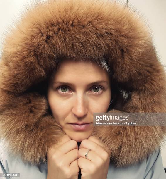 close-up portrait of young woman wearing fur coat - winter coat stock pictures, royalty-free photos & images