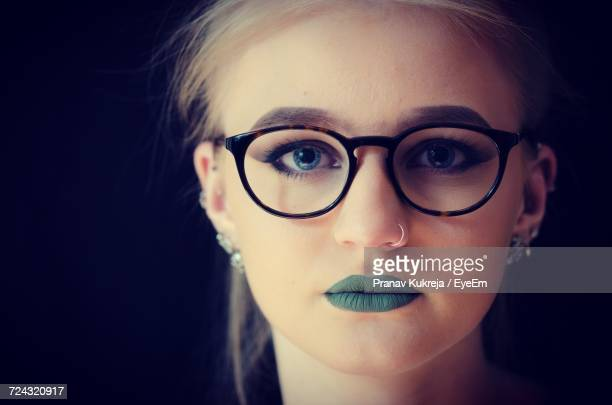 Close-Up Portrait Of Young Woman Wearing Green Lipstick Against Black Background