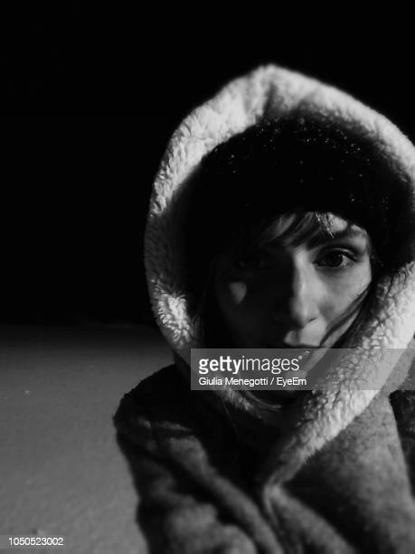 close-up portrait of young woman wearing hooded jacket - clair obscur photos et images de collection