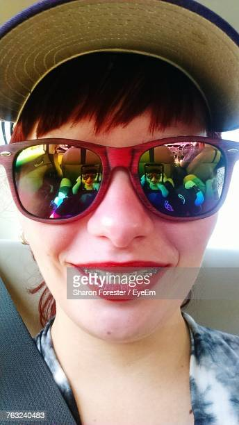 Close-Up Portrait Of Young Woman Wearing Sunglasses In Car