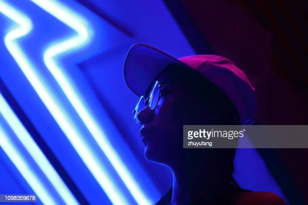 close-up portrait of young woman wearing sunglasses in darkroom - illuminated stock pictures, royalty-free photos & images