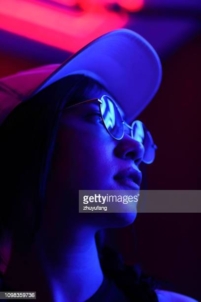 close-up portrait of young woman wearing sunglasses in darkroom - lighting equipment stock pictures, royalty-free photos & images
