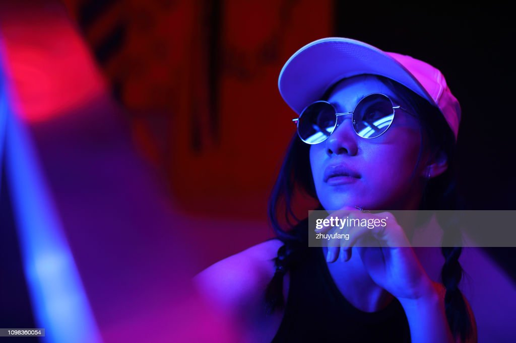 Close-Up Portrait Of Young Woman Wearing Sunglasses In Darkroom : Stock Photo