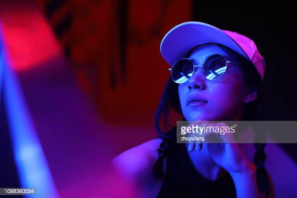 close-up portrait of young woman wearing sunglasses in darkroom - neon stock pictures, royalty-free photos & images