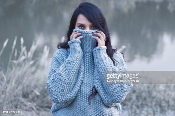 close-up portrait of young woman wearing warm clothing by plants during winter - south asia stock pictures, royalty-free photos & images