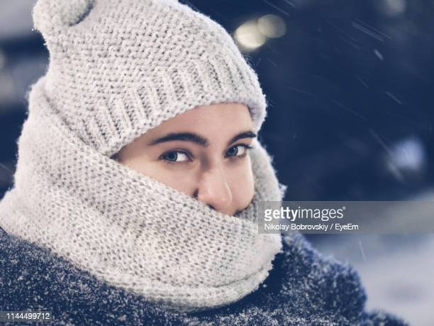 close-up portrait of young woman wearing warm clothing standing outdoors during snowfall - wool stock pictures, royalty-free photos & images