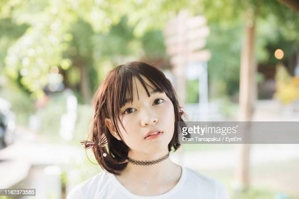 close-up portrait of young woman with bangs in park - short necklace stock pictures, royalty-free photos & images