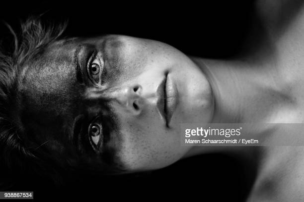 close-up portrait of young woman with face paint against black background - body paint stock-fotos und bilder
